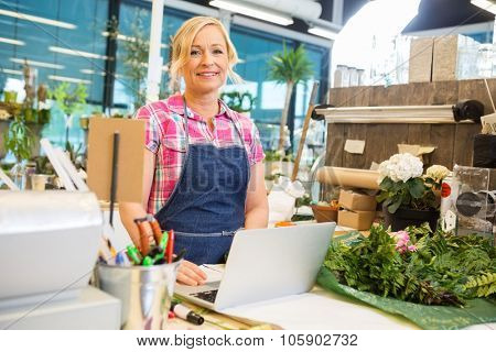 Portrait of smiling mature female florist using laptop at counter in flower shop