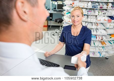 Portrait of smiling mature chemist giving medicine to customer in pharmacy