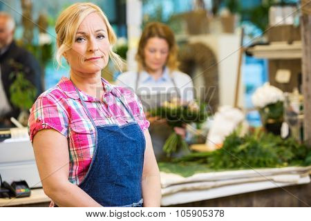 Portrait of mature female florist with colleague working in background at shop