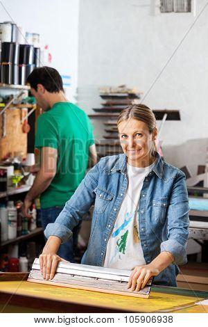 Portrait of confident mid adult woman silkscreening in studio