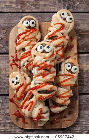 Sausage meatball mummies wrapped in dough and baked. Scary halloween celebration party food covered