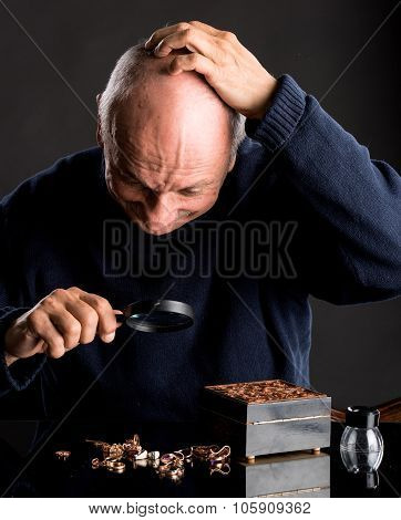 Senior jeweler looking at jewelry through magnifying glass on a dark background poster