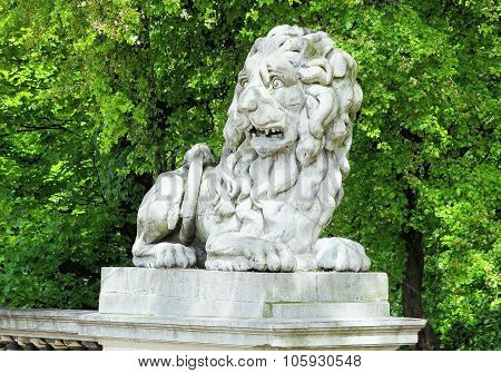 Sculpture of lion in park. Summer tries and sculpture poster