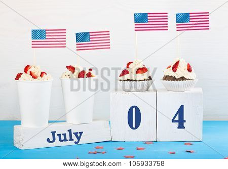 greeting card on the Independence Day of America two cupcakes two desserts with cream strawberries perpetual calendar with the words Jule 4 on a white and blue background
