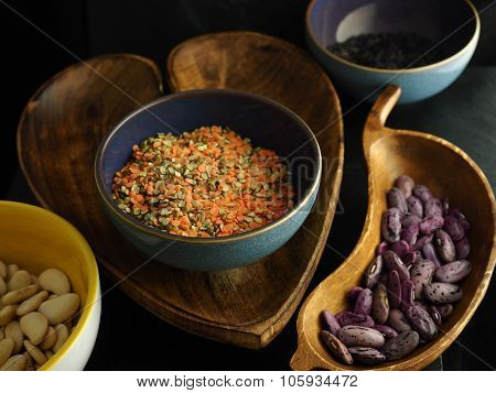 Lentils in a purple bowl with heart shaped wooden bowl and other bowls