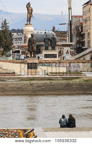 Skopje Macedonia - Marh 20 2014: Skopje Vardar River statues and people relaxing.