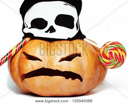 halloween holiday traditional scary smiling orange pumpkin in black skull hat and candys isolated on