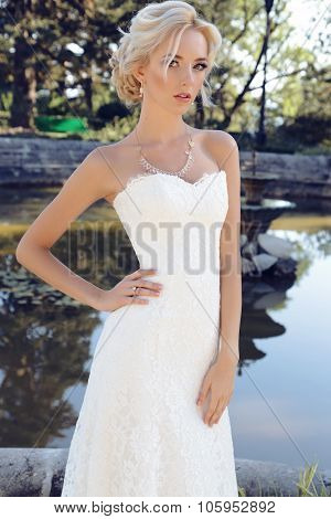 Gorgeous Bride With Blond Hair Wears Luxurious Dress And Accessories