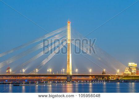 Modern cable-stayed bridge across the Daugava River in Riga night. poster