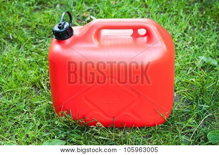 Red Plastic Jerrycan Stands On Green Grass
