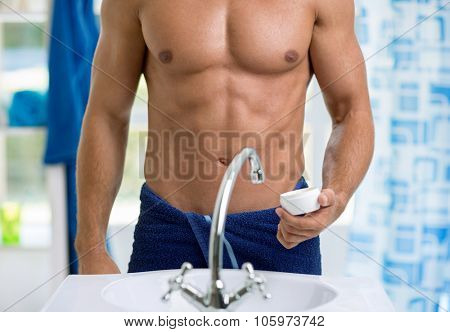 torso of a man standing in front of the bathroom sink poster