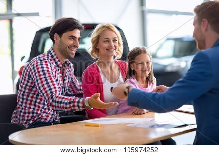 automobile sales center, car dealer selling new automobile to young family with child boy, giving key from the new car daddy