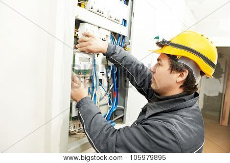 electrician builder at work installing energy saving meter into electric line distribution fuseboard poster