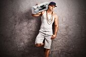Young male rapper in hip-hop outfit listening to music from a ghetto blaster and leaning against a rusty gray concrete wall poster