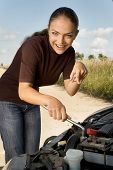 Inexperienced young woman with lug wrench in her hands tries to repair her broken car. poster