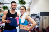 Trainer explaining workout regime to woman at the gym poster
