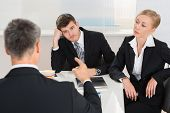 Group Of Three Businesspeople Having Argument At Workplace poster