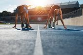 Sprinters at starting blocks ready for race . Athletes at starting position on athletics stadium race track with sun flare. poster