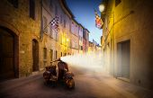 Beautiful street of tuscan San Quirico D'orcia town by night with old-fashioned scooter poster