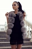 fashion outdoor photo of gorgeous woman with long dark hair wears luxurious fur coat posing on stairs poster