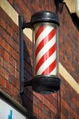 The origin of the barber pole is associated with blood letting. In medieval times barbers performed surgery as well as tooth extraction. The red and white stripes represents bandages and blood poster