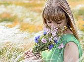 Young sensual girl smelling a bouquet of wildflowers poster