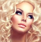 Beauty Girl With Healthy Long Curly Hair. Blonde Woman Portrait with blue eyes. Blond Wavy permed Hair and bright makeup, vivid make-up, smoky eyes and false eyelashes. Holiday make up. Perfect skin poster