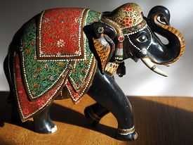 Painted wooden elephant on a wooden table in sunlight