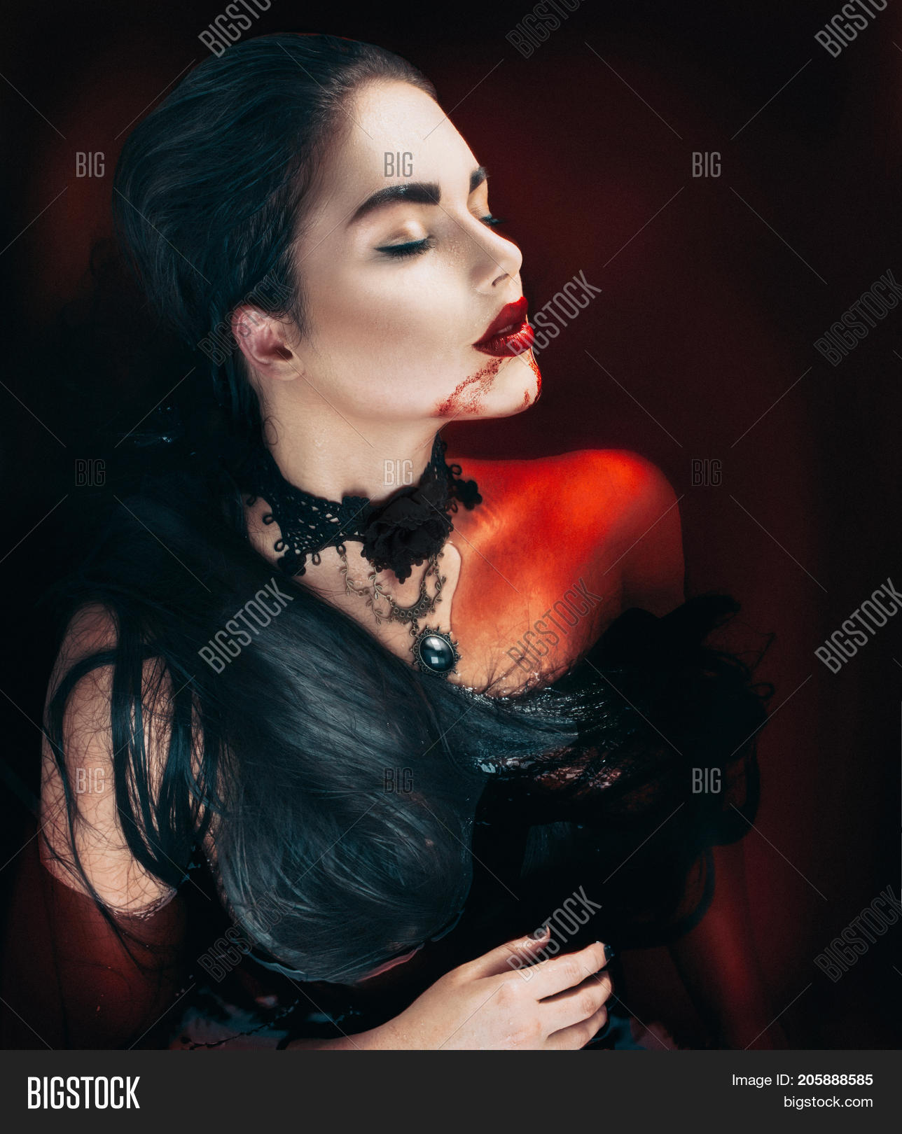 Beauty halloween sexy vampire woman with dripping blood on her mouth lying in a bath full