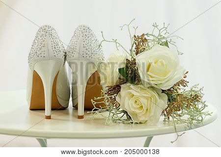 Wedding shoes with rhinestones and flowers on a table