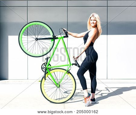 Fitness princess with long hair girl in black sexy outfit and sneakers lifted up vintage green bicycle fix. Outdoor.