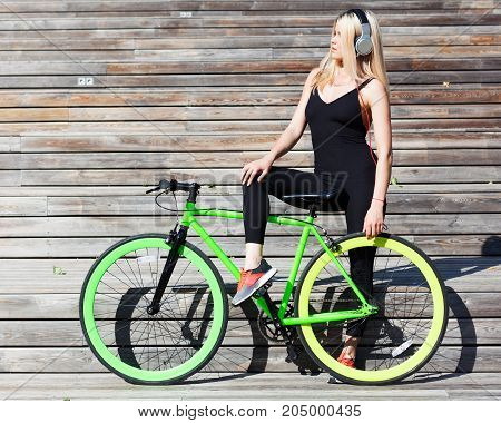 Fitness princess with hair blond girl in black skin-tight sexy outfit and shoes resting on the wooden steps with fashionable fix bicycle listening to music with headphones on a sunny day. Outdoor.