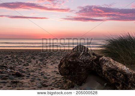 Sunset on the west coast of the united kingdom north wales. Rock in the foreground sand and pebbles grass to right of frame. Calm sea. Mainly clear sky with light fluffy clouds.