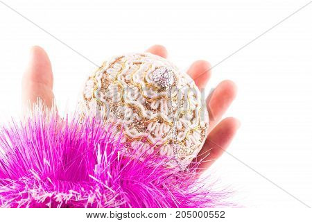 christmas toy bright and beautiful in hand on a white background in front of her purple fluffy decoration