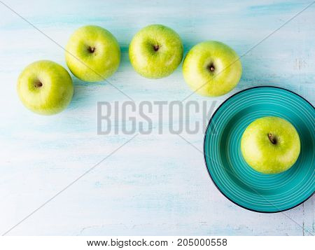 Green pastel background with apples flowers. Healthy food concept backdrop for writing text. Top view