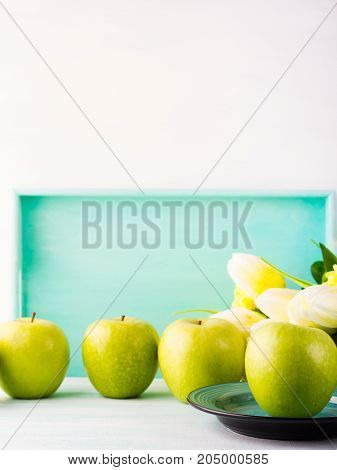 White green pastel background with apples yellow flowers. Healthy food concept backdrop for writing text