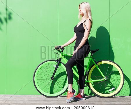Beauty blonde girl with long hair in a black tight-fitting sexy outfit and sneakers posing with a fashionable fix bicycle background of a green wall on a sunny summer day. Outdoor.