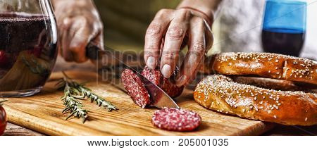 Traditional Italian Red Wine, Salami, Rosemary, Bread. Close Up Of A Person's Hand Cut Salami On A K