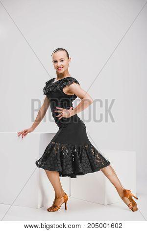 passionate girl in black dress dancing in studio, woman posing sitting