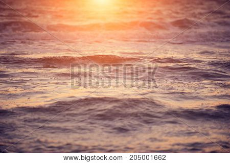 Soft wave of sea at warm gold sunset light. Selective focus.