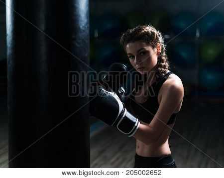 Young fighter boxer girl wearing boxing gloves in training with heavy punching bag.