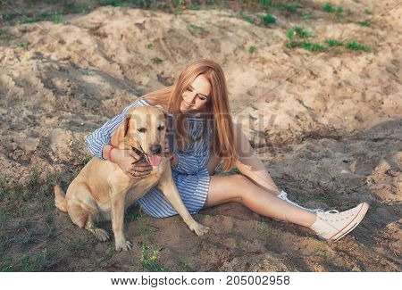 Portrait Of Young Beautiful Woman In Sneakers Sitting On Sand Beach Hugging Golden Retriever Dog. Gi