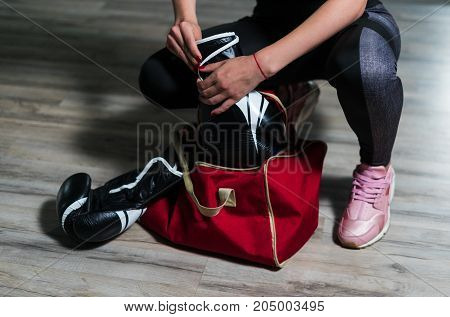 Young fighter boxer girl puting on boxing gloves before  training. She has sport bag