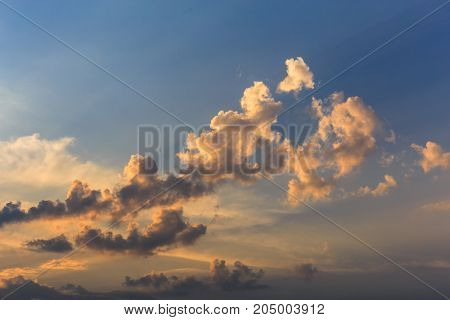 Cumulus sunset clouds with sun setting down, toned