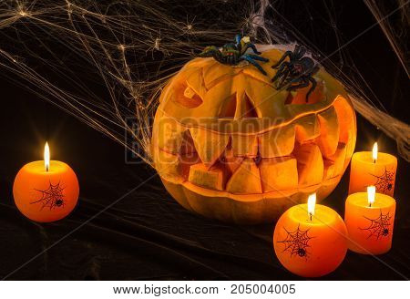 There are the horrible pumpkin and burning orange candles on a black table.Everything prepares for the holiday of Halloween