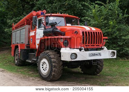Voronezh, Russia, September 8, 2017: Russian red truck firefighter automobile at green trees background