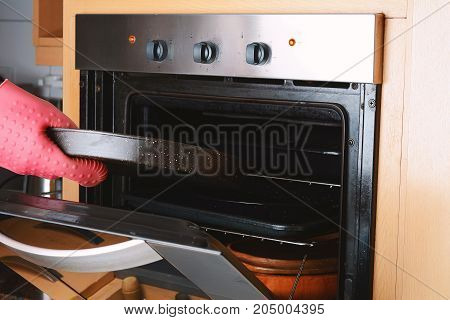 Taking Baked Tray Out Of Oven With Kitchen Gloves