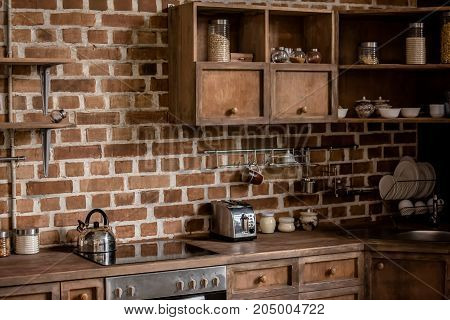 Stylish kitchen interior with brick wall and wooden furniture brown color scheme