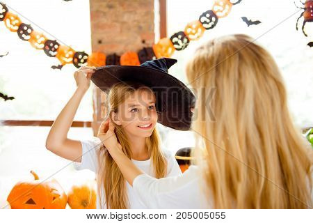 Close Up Of Charming Small Blonde Girl In A Black Witch Hat, Mom Is Fixing Her Hair With Such Love,