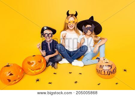 Boo! Portrait Of Blond Mum With Two Small Kids Siblings, Dressed In Scary Costumes, Eyewear, Sitting